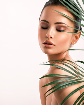 Young beautiful woman with green leaves near body. Skin care beauty treatments concept.  Closeup girl's face with green leaves.