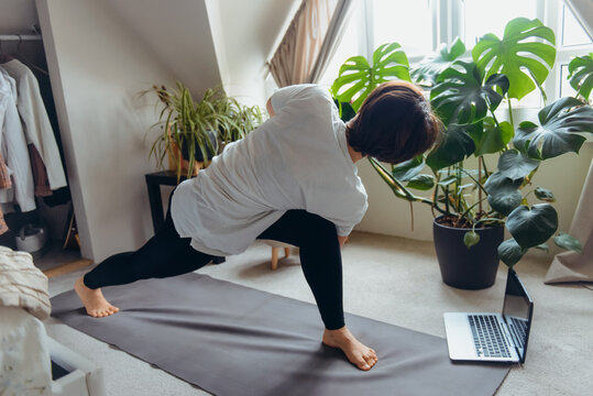 A woman on a mat doing twist and stretching asana position in her bedroom. Online class yoga practice at home. Healthy Lifestyle. Home online workout during a lockdown. Soft selective focus.