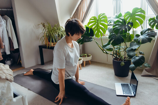 A woman on a mat trying to do a twine asana position in her bedroom with plants. Online class yoga practice at home. Healthy Lifestyle. Home online workout during a lockdown. Soft selective focus.