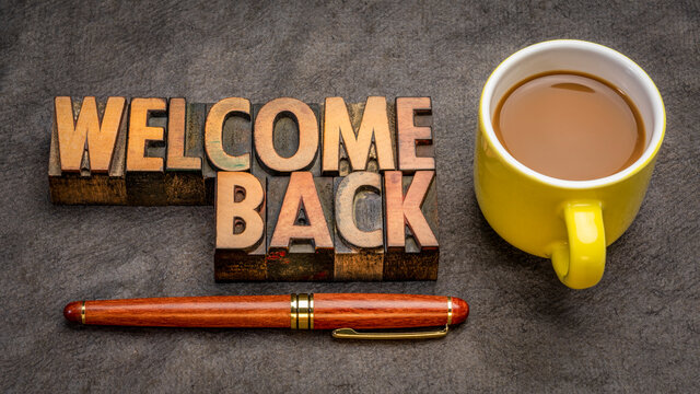 Welcome back sign - text in vintage letterpress wood type with a cup of coffee against handmade paper, greetings and business reopening concept