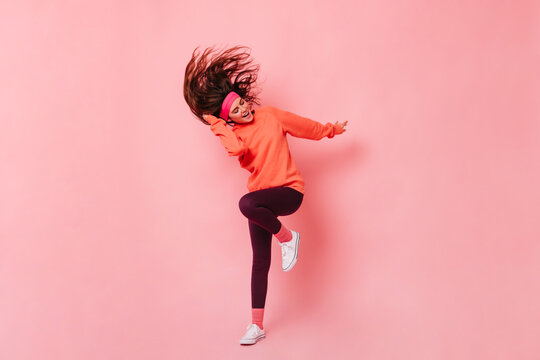 Energetic fitness instructor demonstrates exercises to warm up. Woman in bright tracksuit doing aerobics