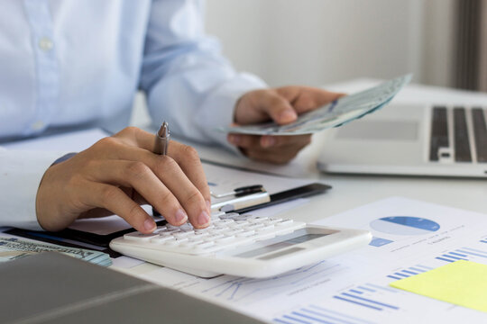 Business woman using a white calculator. She is analyzing the company's annual results in detail. In order to make the information accurate and complete without making any errors.