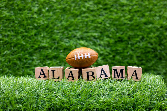 American football with ALABAMA word on green grass