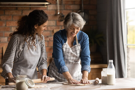 Happy mature grey haired woman with grownup daughter wearing aprons cooking handmade pastry, rolling dough, chatting, having fun, standing in kitchen at home, family spending leisure time together
