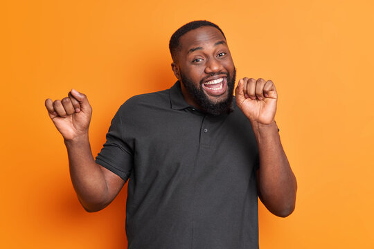 Studio shot of carefree positive black man with thick beard dances carefree has upbeat mood raises arms enjoys favorite music isolated over vivid orange wall. Afro American guy moves actively indoor