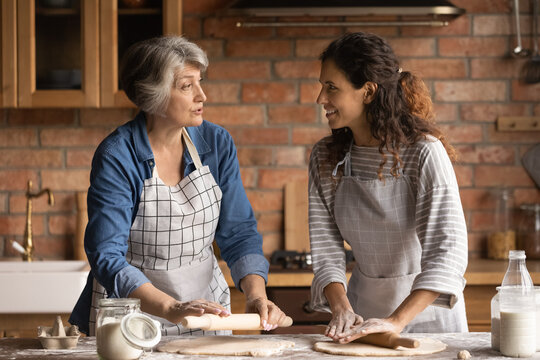 Mature grey haired woman with grownup daughter chatting, cooking homemade pastry, rolling dough, standing in kitchen at home, family spending leisure time together, preparing pie or bread together