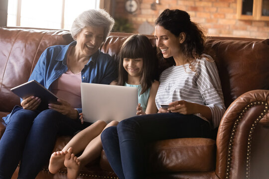 Happy three generations of women having fun with gadgets together, browsing apps, sitting on cozy couch at home, smiling little girl with mother using laptop, mature grandmother holding tablet