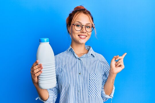 Young redhead woman holding liter bottle of milk smiling happy pointing with hand and finger to the side
