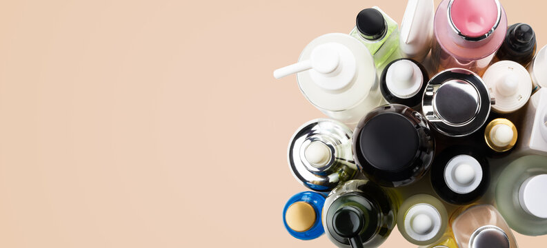 Many cosmetics tubes top view banner on biege skin tone background, copy space.