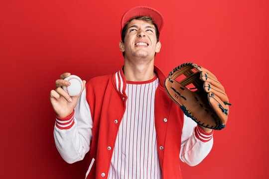 Handsome caucasian man wearing baseball uniform holding golve and ball angry and mad screaming frustrated and furious, shouting with anger looking up.