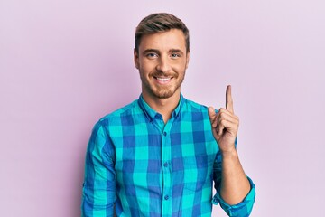 Handsome caucasian man wearing casual clothes pointing finger up with successful idea. exited and happy. number one. Wall mural