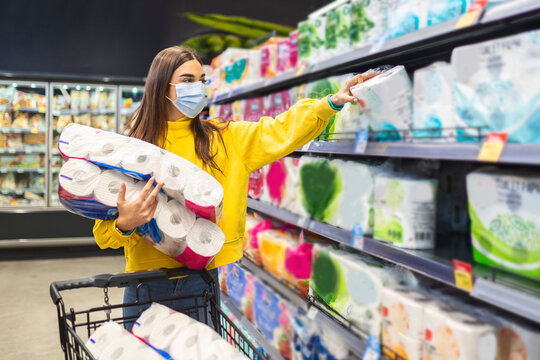 Toilette paper shortage.Woman with hygienic mask shopping for toilette paper supplies due to panic buying and product hoarding during virus epidemic outbreak.Hygiene products deficiency stock photo