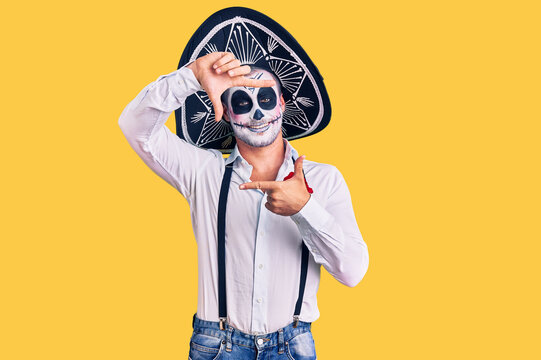 Man wearing day of the dead costume over background smiling making frame with hands and fingers with happy face. creativity and photography concept.
