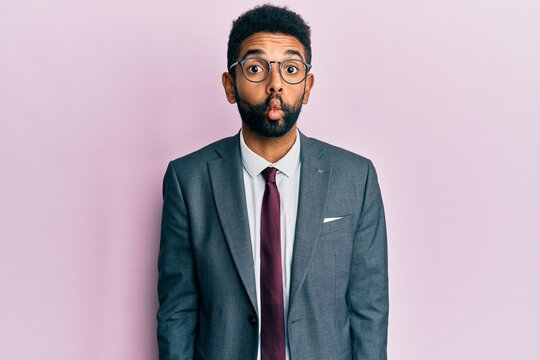 Handsome hispanic business man with beard wearing business suit and tie making fish face with lips, crazy and comical gesture. funny expression.