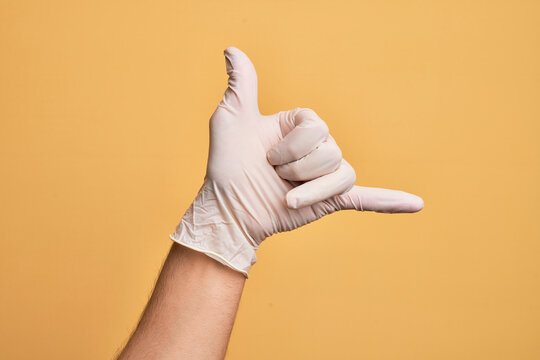 Hand of caucasian young man with medical glove over isolated yellow background gesturing Hawaiian shaka greeting gesture, telephone and communication symbol