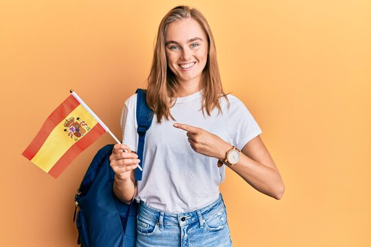 Beautiful blonde woman exchange student holding spanish flag smiling happy pointing with hand and finger
