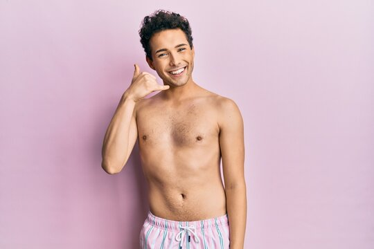 Young handsome man wearing swimwear shirtless smiling doing phone gesture with hand and fingers like talking on the telephone. communicating concepts.