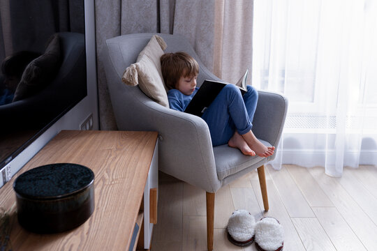 Cute preschool blonde kid reading book sitting on a cozy chair in light nordic style living room