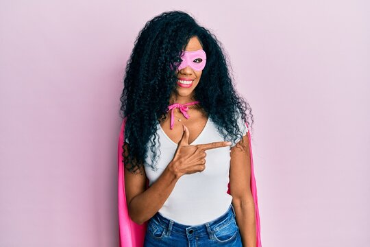 Middle age african american woman wearing super hero costume cheerful with a smile of face pointing with hand and finger up to the side with happy and natural expression on face