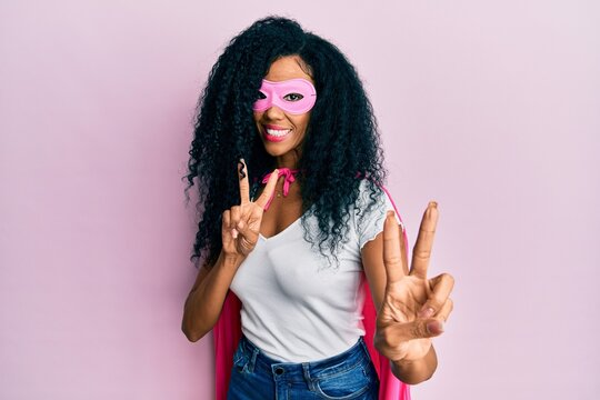 Middle age african american woman wearing super hero costume smiling looking to the camera showing fingers doing victory sign. number two.