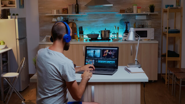 Creative filmmaker editing video footage in home using modern technology. Man content creator in home working on montage of film in new software for editing late at night.