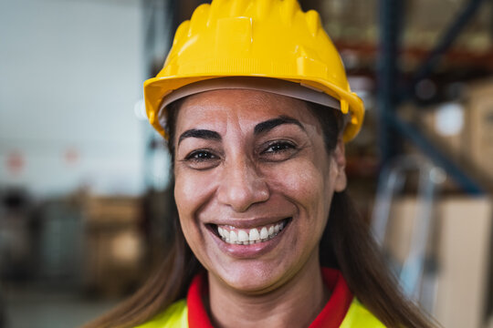 Portrait of happy Latin woman working in delivery warehouse - Logistic and industry concept