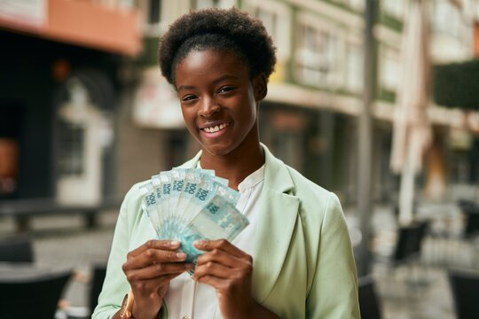Young african american businesswoman smiling happy holding brazilian real banknotes at the city