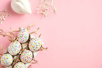 Happy Easter concept. Cute Easter eggs, bunny and spring flowers on pink table. Flat lay, top view,...