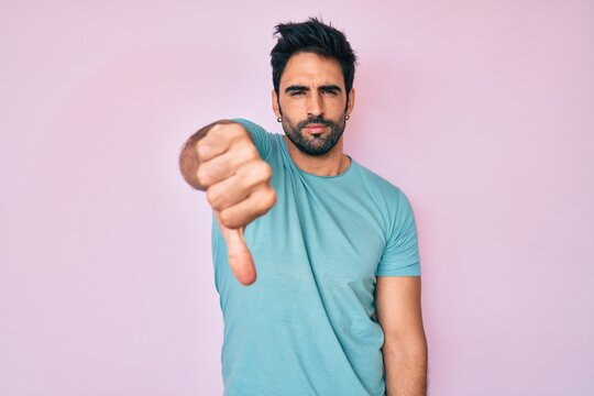 Handsome hispanic man with beard wearing casual clothes looking unhappy and angry showing rejection and negative with thumbs down gesture. bad expression.