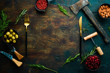 Dark kitchen background with spices and kitchen utensils. Free copy space. Top view.