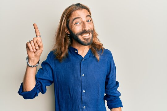 Attractive man with long hair and beard wearing casual clothes smiling with an idea or question pointing finger up with happy face, number one