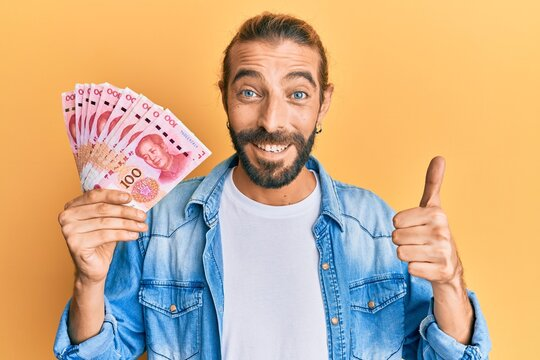 Attractive man with long hair and beard holding 100 yuan chinese banknotes smiling happy and positive, thumb up doing excellent and approval sign