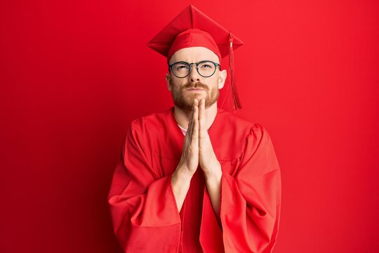 Young redhead man wearing red graduation cap and ceremony robe begging and praying with hands together with hope expression on face very emotional and worried. begging.