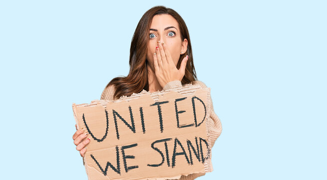 Young brunette woman holding united we stand banner covering mouth with hand, shocked and afraid for mistake. surprised expression