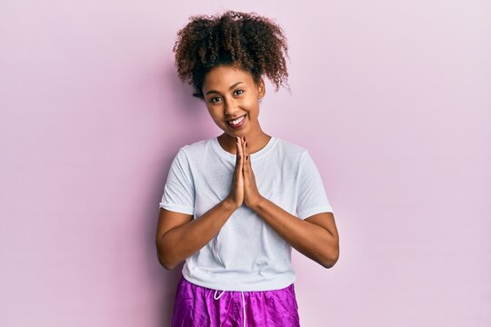 Beautiful african american woman with afro hair wearing sportswear praying with hands together asking for forgiveness smiling confident.