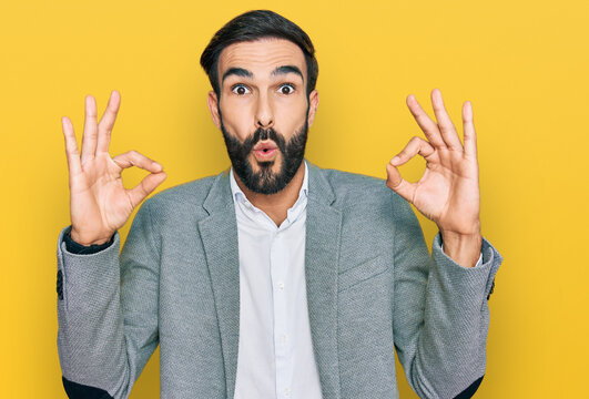 Young hispanic man wearing business clothes looking surprised and shocked doing ok approval symbol with fingers. crazy expression