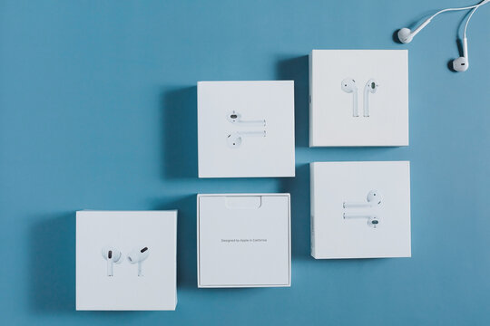 Surgut / Russia - October 29, 2020 : Flat lay of different generation of iPhone headphones (airpods and pro) boxes are on a blue background. The concept of the packaging of apple products.