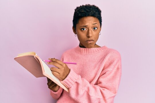 Young african american girl reading and writing book skeptic and nervous, frowning upset because of problem. negative person.