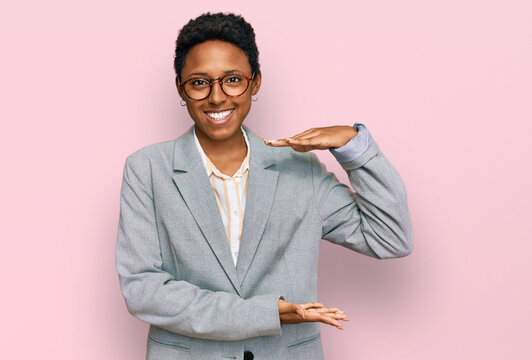 Young african american woman wearing business clothes gesturing with hands showing big and large size sign, measure symbol. smiling looking at the camera. measuring concept.