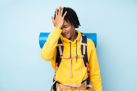 Young mountaineer african american man with a big backpack isolated on a blue background having doubts with confuse face expression