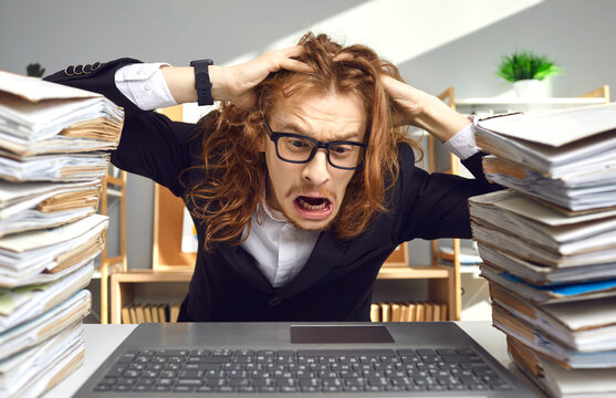 Crazy weird stressed young guy in glasses having busy day at work, sitting at office desk with computer, tearing hair in despair exhausted by much paperwork, huge file archive, red tape workload chaos