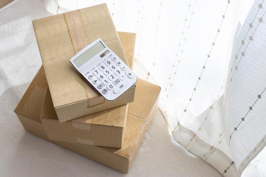 電卓とダンボール、荷物費用イメージ