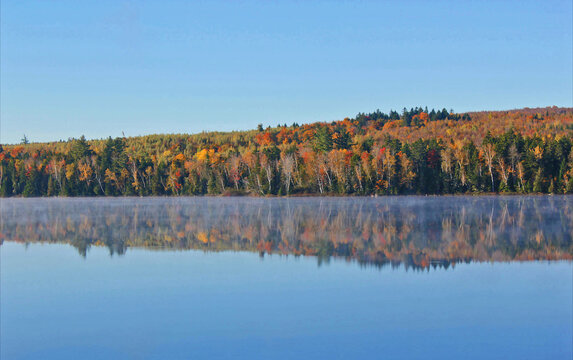 Autumn colors across lake with misty water