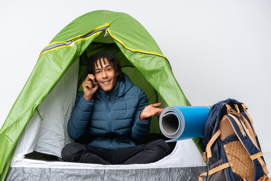 Young african american man inside a camping green tent keeping a conversation with the mobile phone with someone
