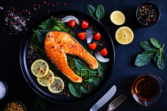 Fried salmon steak with spinach, lemon and cherry tomatoes  served on black plate on wooden table
