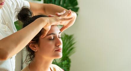 Fototapeta Healthcare spa and massage thai concept. Close up hands of thai masseuse woman getting massage head for customer. Face massage treatment in the spa salon, Girl receiving holistic massage treatment. obraz
