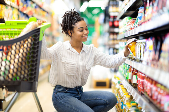 African Woman Choosing Products Doing Grocery Shopping In Supermarket