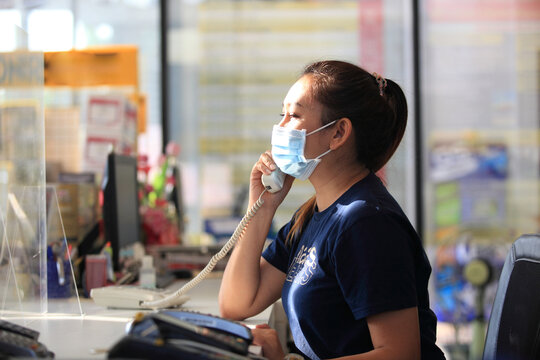Young woman with face mask back at work in office after lockdown