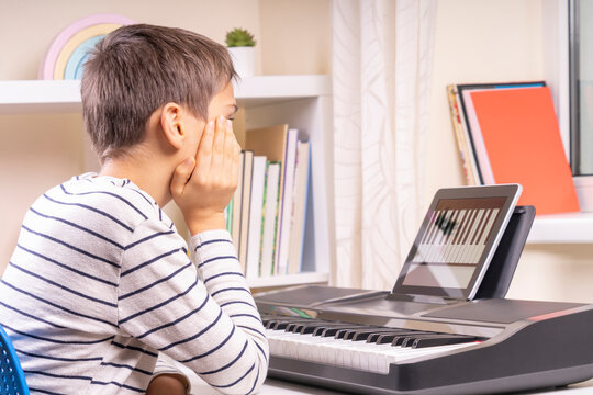 Teenage boy watching video lesson at tablet computer and learing playing digital piano at home. Online learning remote education