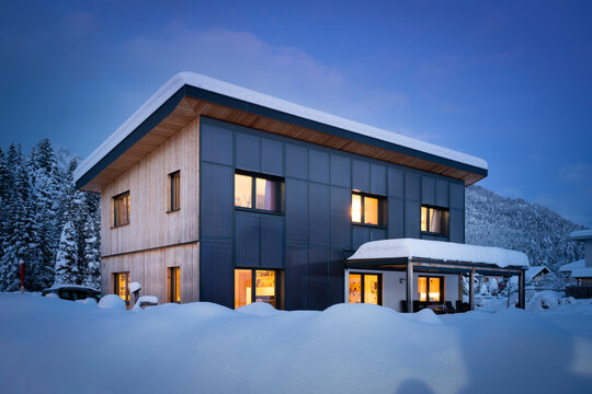 Climate-neutral solar house with self-sufficient and sustainable heating and hot water preparation at night in snowy winter